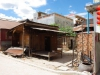 Net buiten het complex wonen de Cambodjanen in eenvoudige, golfplaten huisjes; het bed staat buiten