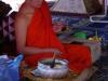 Kaarsjes op schalen met bloemblaadjes, die vervolgens door een monnik worden gezegend