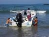 Drie mensen houden, staand in het water, de boot op haar plaats