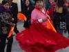 Een optocht  met fraai uitgedoste mensen die dansen op de muziek van de fanfare