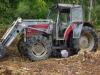 Een bosarbeider ligt vloekend en steunend, nat van de regen, onder zijn tractor