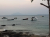 Bootjes dobberen voor de kust, terwijl de avond valt