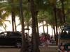 Auto's zijn het strand opgereden en staan zo opgesteld dat de inzittenden door de voorruit de zon kunnen zien ondergaan