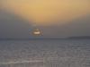 De zon zakt achter het meer