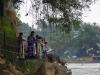 Op de kade staan Vietnamezen in klederdracht te offeren aan de Moeder van het Water