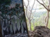 Phnom Dampeau, een bizar schilderij aan een boom, van mensen die van rotsen worden afgegooid