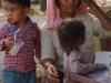 Een moeder met haar kinderen schuift aan