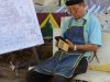 Een kunstenaar biedt zijn werk te koop aan voor het Sisaket Museum