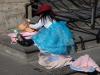 Voor de kerk verkoopt een Peruviaanse souvenirs, terwijl haar dochtertje de pop in bad doet