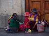 Naast de kerk verkopen Peruviaanse vrouwen met hun kinderen snoep