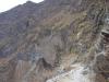 Het pad is stoffig, slingert in haarspeldvorm naar beneden en gaat al vrij snel over in kiezels, keien en rotsen