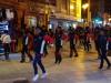 Een optocht  met fraai uitgedoste mensen en krijgers die dansen op de muziek