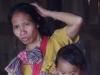 Een vrouw met kind komt het terras op
