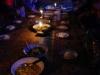 Gezeten op de grond, verlicht door kaarsen, eten we kip-currie